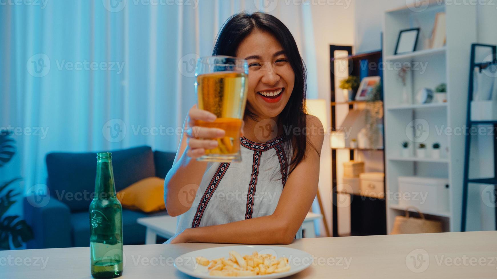 joven asiática bebiendo cerveza divirtiéndose feliz noche fiesta evento de año nuevo celebración en línea a través de videollamada por teléfono en casa por la noche. distancia social, cuarentena por coronavirus. punto de vista o pov foto