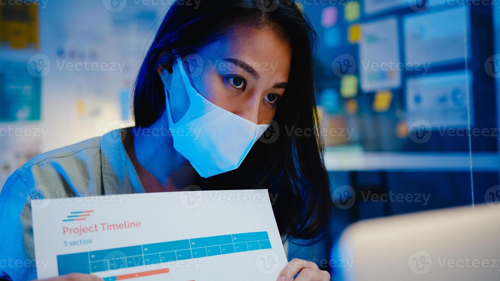 Asia empresaria distanciamiento social en una nueva situación normal para la prevención mientras usa la presentación de la computadora portátil a sus colegas sobre el plan en la videollamada mientras trabaja en la noche de la oficina. vida después del virus corona. foto