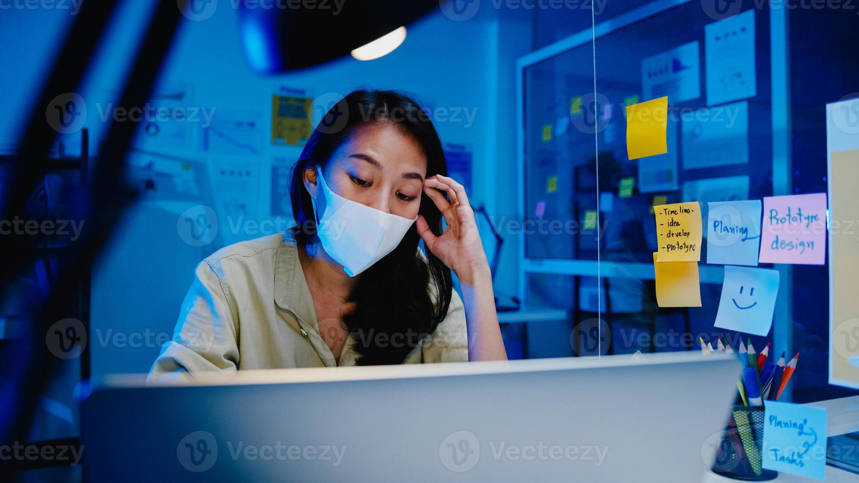 Las mujeres asiáticas independientes usan mascarilla usando una computadora portátil en el trabajo duro en la nueva oficina normal. trabajo desde casa sobrecarga nocturna, autoaislamiento, distanciamiento social, cuarentena para la prevención del virus corona. foto