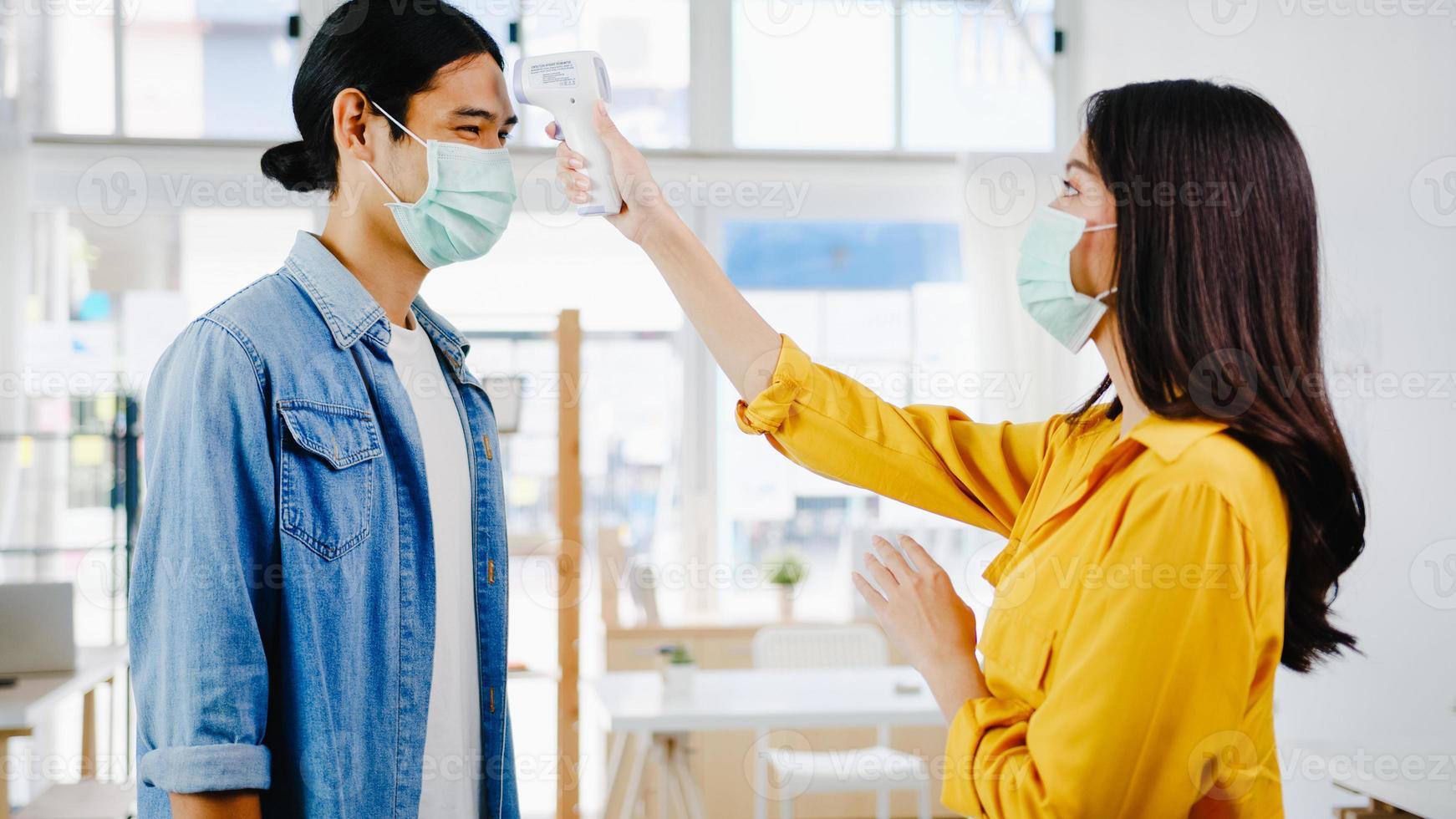 Recepcionista de asia que lleva a cabo el uso de una máscara protectora, use un termómetro infrarrojo o una pistola de temperatura en la frente del cliente antes de ingresar a la oficina. estilo de vida nuevo normal después del virus corona. foto