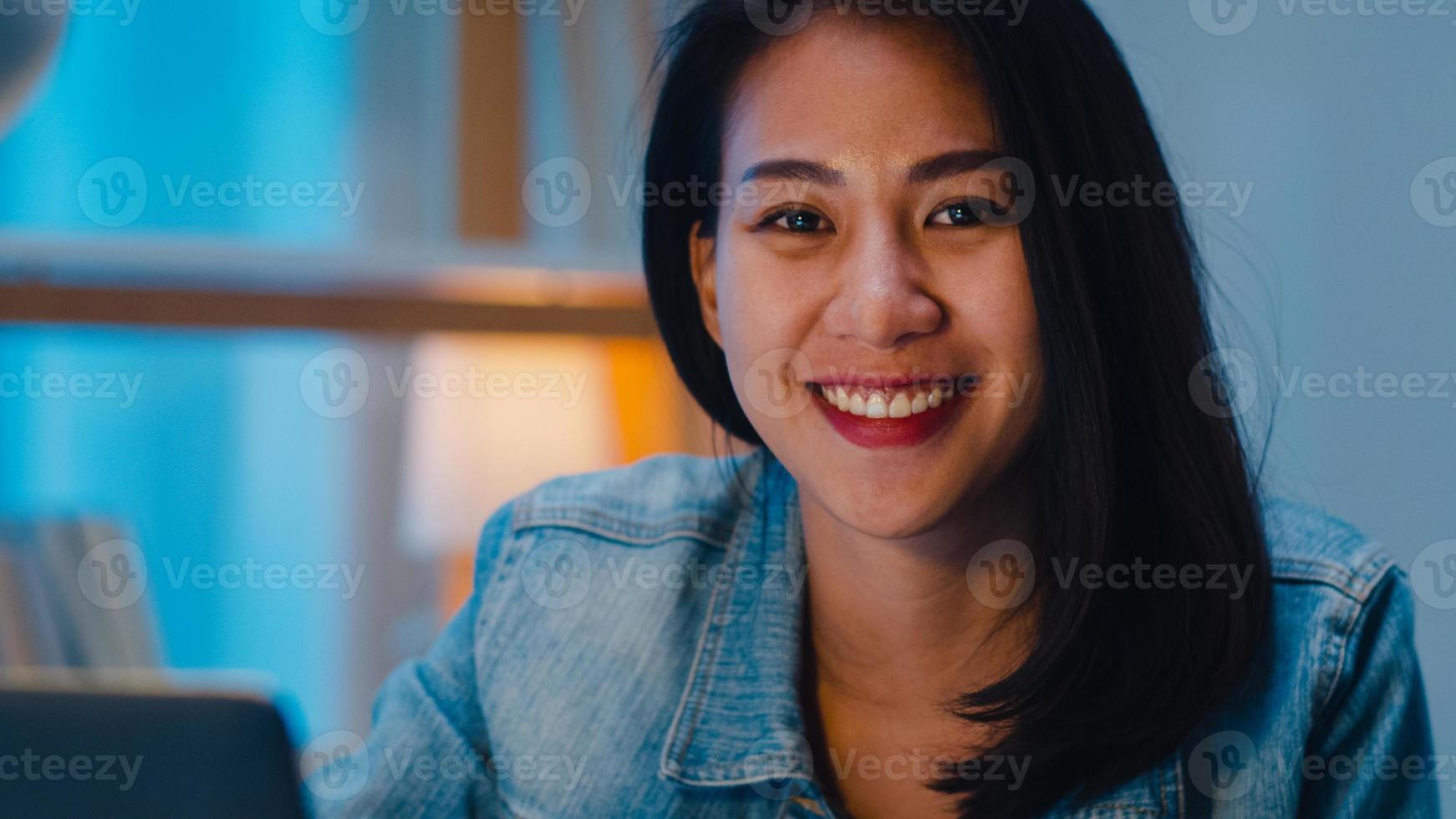 Señora joven alegre del diseñador gráfico que usa la tableta gráfica digital mientras trabaja hasta tarde en la oficina moderna por la noche, mujer profesional de Asia que usa el retocador de la computadora portátil que se sienta en la sala de estar en casa. foto