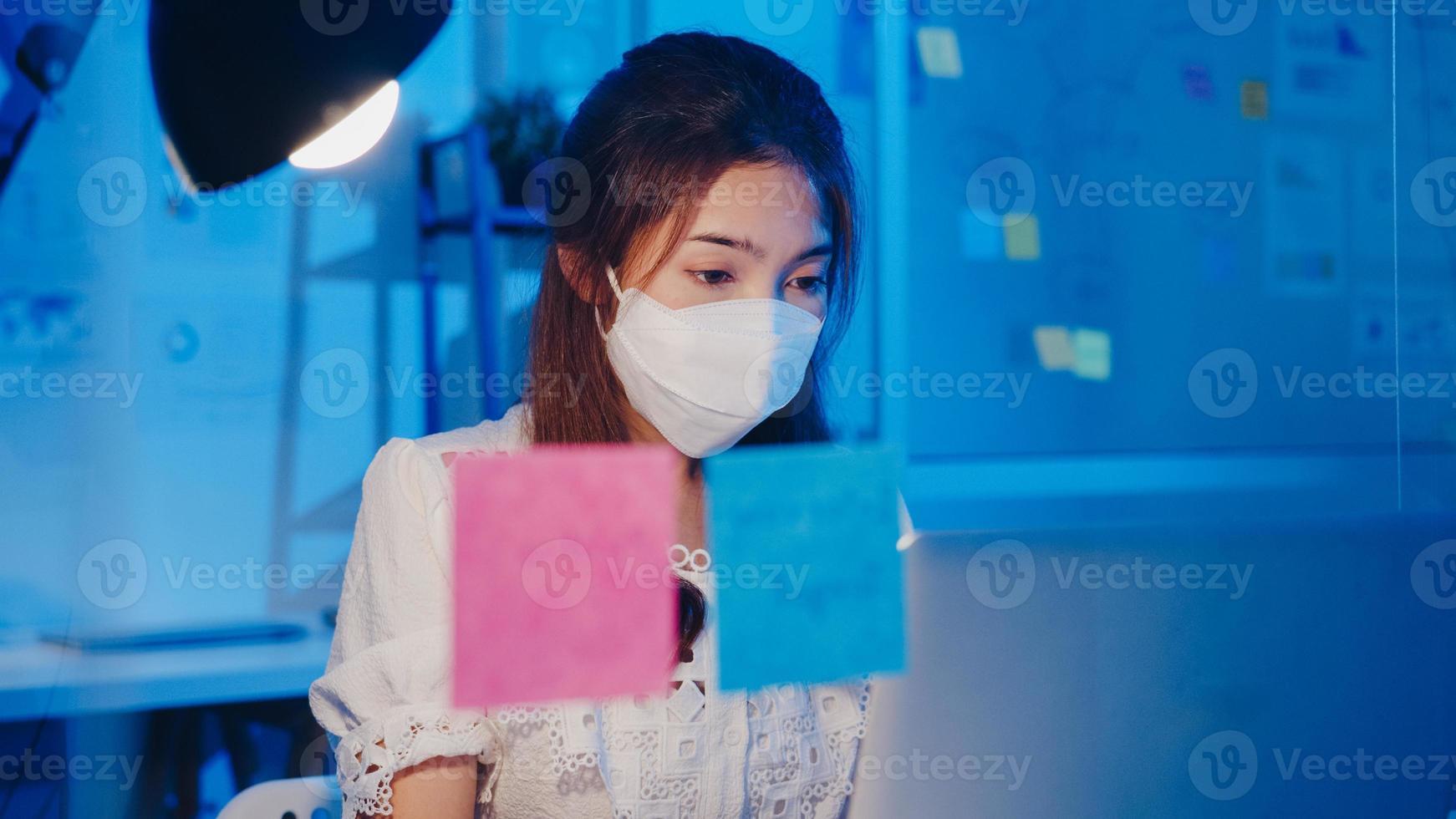 Feliz empresaria asiática con mascarilla médica para el distanciamiento social en una nueva situación normal para la prevención de virus mientras usa la computadora portátil en el trabajo en la noche de la oficina. vida y trabajo después del coronavirus. foto