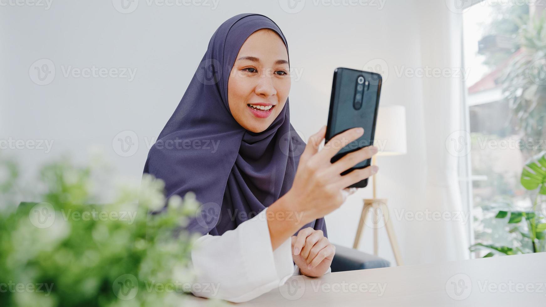 Joven empresaria musulmana asiática que usa un teléfono inteligente, habla con un amigo por videochat y realiza una lluvia de ideas en línea mientras trabaja de forma remota desde su casa en la sala de estar. distanciamiento social, cuarentena por coronavirus. foto