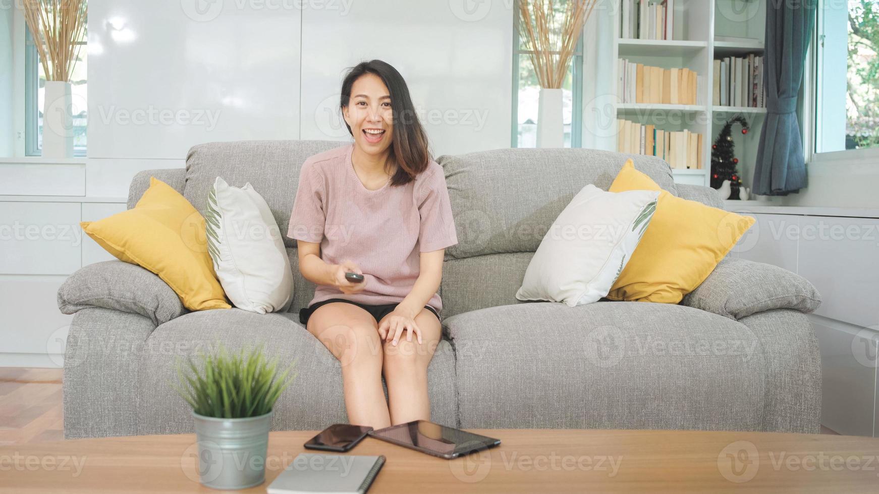 Joven mujer asiática adolescente viendo la televisión en casa, mujer sintiéndose feliz acostado en el sofá en la sala de estar. mujer de estilo de vida relajarse por la mañana en el concepto de hogar. foto