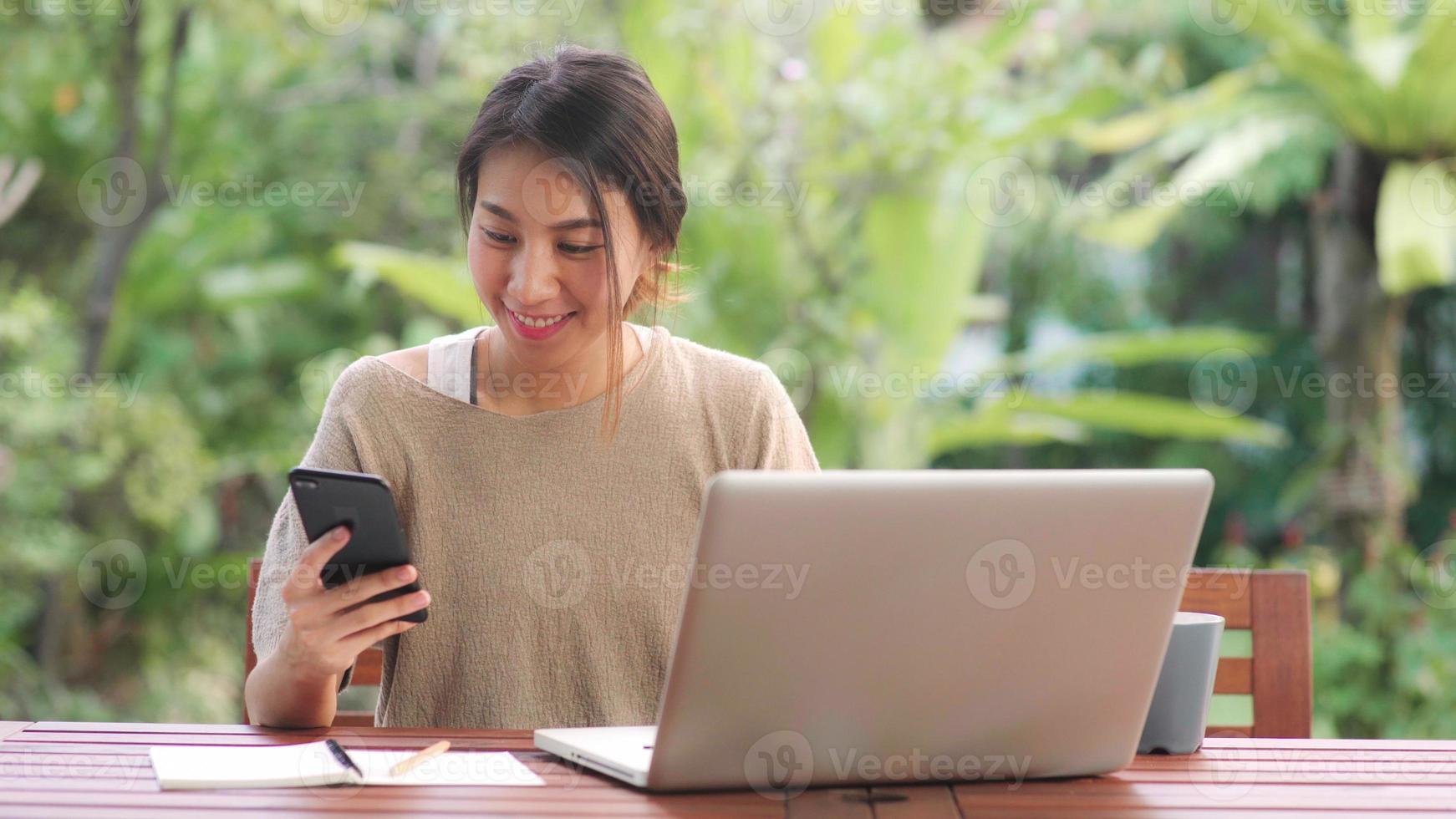 mujer asiática independiente que trabaja en casa, mujer de negocios que trabaja en la computadora portátil y que usa el teléfono móvil tomando café sentado en la mesa en el jardín por la mañana. mujeres de estilo de vida que trabajan en el concepto de hogar. foto