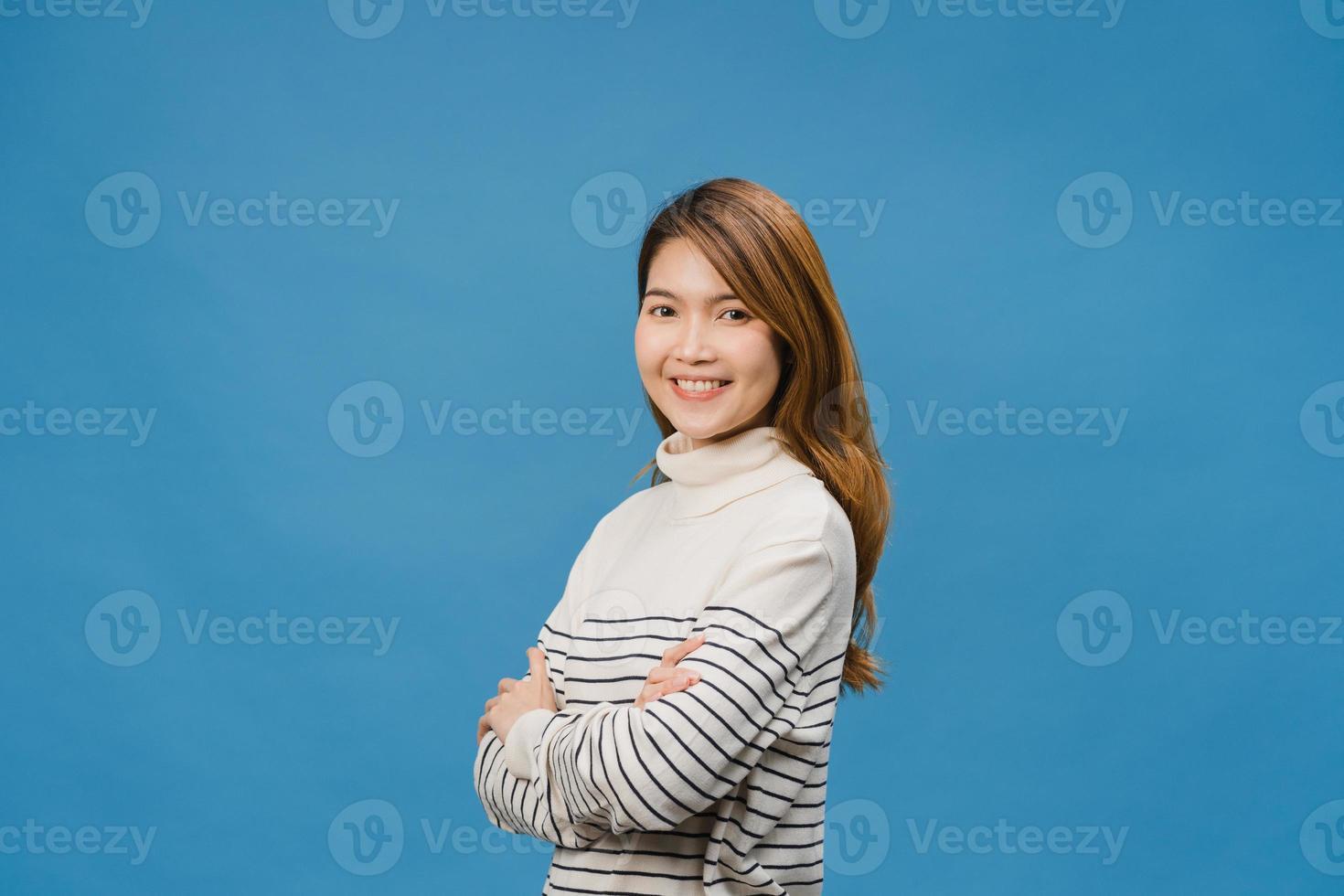 Retrato de una joven asiática con expresión positiva, con los brazos cruzados, una amplia sonrisa, vestida con ropa informal y mirando a la cámara sobre fondo azul. feliz adorable mujer alegre se regocija con el éxito. foto