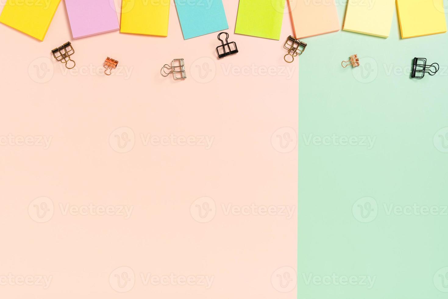 espacio de trabajo mínimo: foto creativa plana del escritorio del espacio de trabajo. Escritorio de oficina de vista superior con nota adhesiva sobre fondo de color rosa verde pastel. vista superior con espacio de copia, fotografía plana.