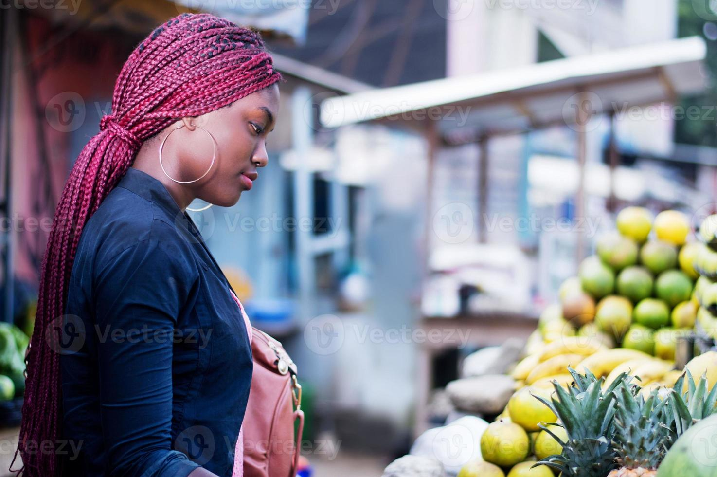 beautiful young woman at the fruit market of the street photo