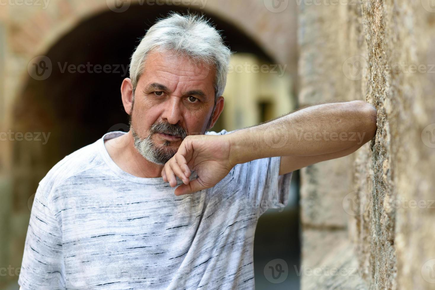 Mature man looking at camera in urban background photo