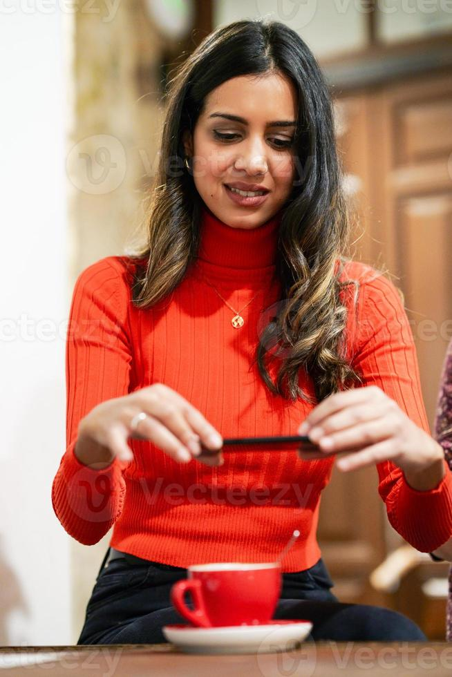 Arab young woman using smartphone in a cafe bar. photo