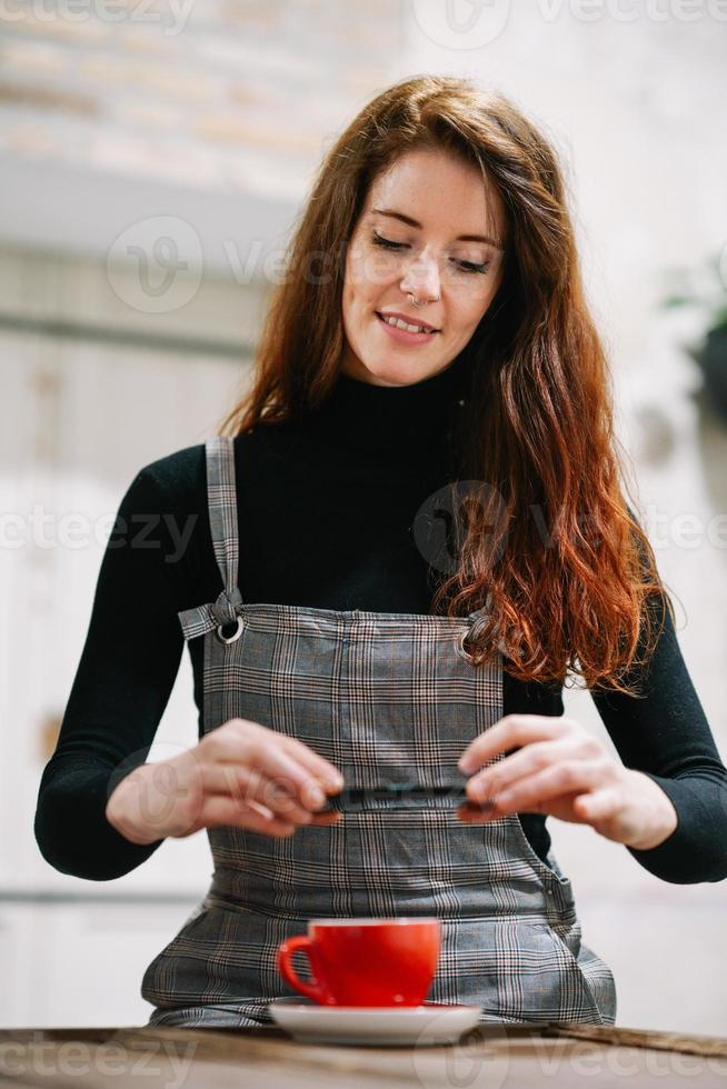 Redheaded woman with some gray hair using smartphone in a cafe. photo