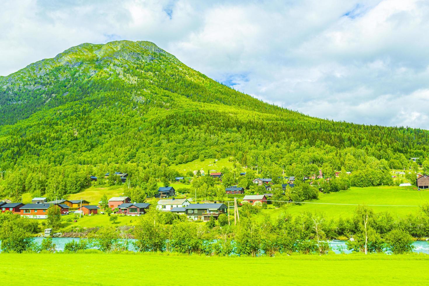 El agua de deshielo turquesa fluye en un río a través de una aldea en Noruega. foto
