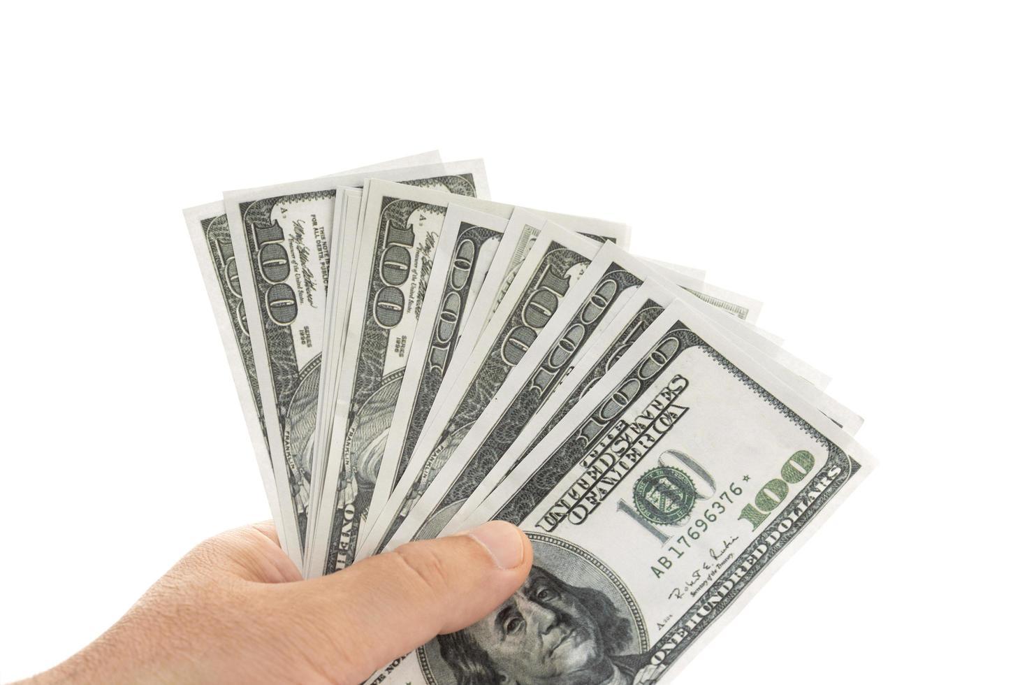 Mano sujetando billetes de dinero aislado sobre fondo blanco. foto
