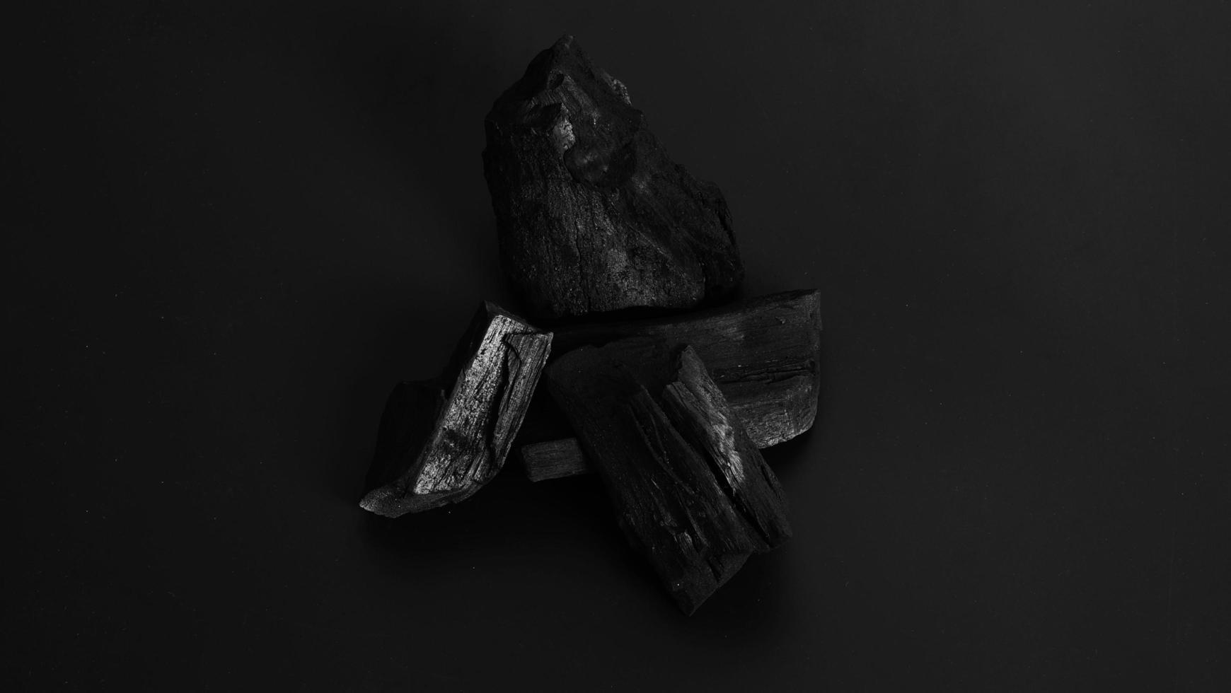 carbón de leña. carbón negro sobre piso texturizado negro. utilizado para cocinar foto
