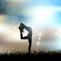 Het silhouet van een wijfje in een yoga stelt in zonnig landschap