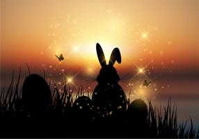 Easter bunny sat in grass against a sunset sky vector