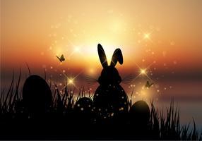 Coelhinho da Páscoa sentou-se na grama contra um céu do sol