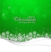 Tarjeta de felicitación de la feliz Navidad con el fondo verde del copo de nieve