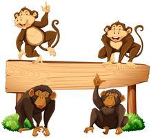 Cuatro monos y cartel de madera. vector