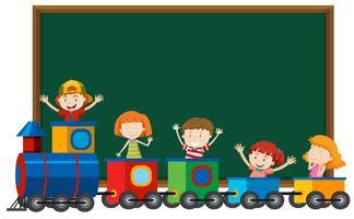 Children in train infront of blackboard
