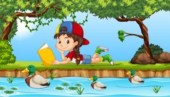 Una niña leyendo un libro junto al río.