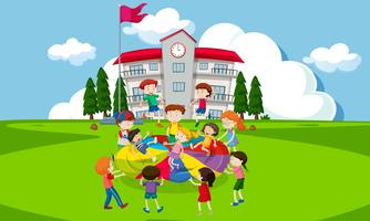 Niños jugando con un paracaídas delante de la escuela.