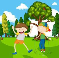 Två pojkar som spelar jumprope i parken