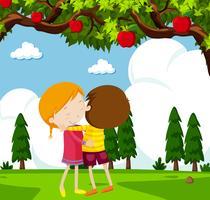Pojke och flicka kramar under äppelträd