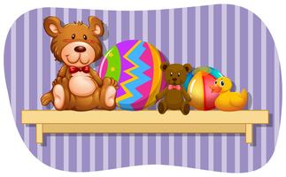 Teddybears and balls on wooden shelf