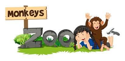 Mono y niña por el signo del zoológico