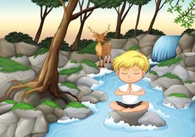 Un niño medita en la naturaleza.