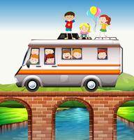 Children riding on camper van over the bridge