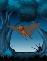 Um morcego voando na floresta escura