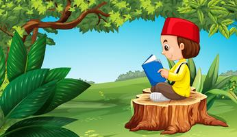 Muslim boy reading book in park