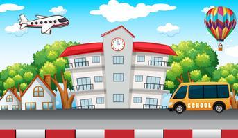 Edificio escolar con bus escolar en frente.