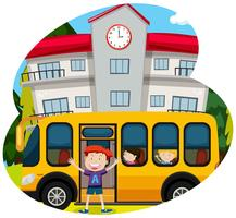Glad pojke infornt av en skolbuss
