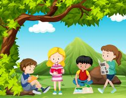 Cuatro niños leyendo libros debajo del árbol