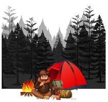 En man camping i mörk skog