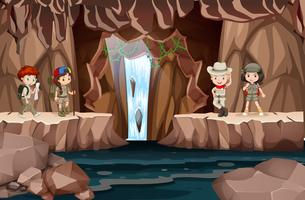 Children exploring a cave with waterfall