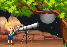 Niño mirando a través del telescopio en la noche