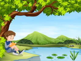 Boy reading book by the pond