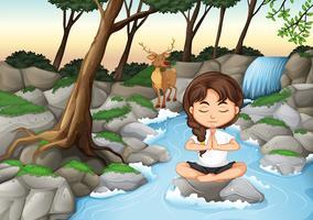 Una niña medita en la naturaleza.