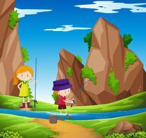 Två barn fiskar vid floden