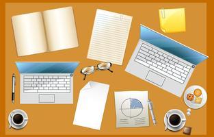 Kontorsbord fullt med papper och datorer