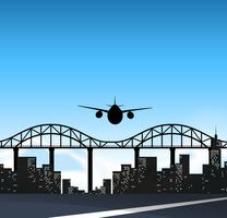 Airplane flying over the bridge in the city