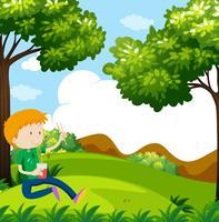 Pojke som äter nudlar i parken