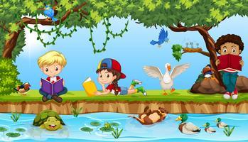Niños leyendo libro nexe al rio
