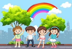 Happy children in the park with rainbow in sky