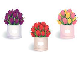 Blumensträuße mit bunten Tulpen in runden Hutschachteln.