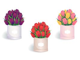 Bouquets of colorful tulips in round hat boxes.